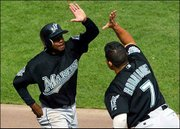 Florida's Juan Pierre gets a high five from teammate Ivan Rodriguez after scoring a first-inning run.
