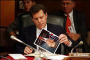 U.S. Sen. Sam Brownback, R-Kan., autographs pictures of himself during a Senate Appropriations hearing on the budget for the war in Iraq. The Sept. 22 hearing featured testimony by Paul Bremer, the American civilian administrator of Iraq.