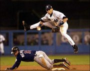 New York shortstop Derek Jeter leaps over Minnesota's Doug Mientkiewicz but is unable to turn a double play in the sixth inning. The Yankees won Game 2 of their American League division series, 4-1, Thursday in New York.