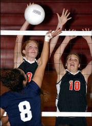 Lawrence High's Carolyn Raynes, left, and Elise McDonald block a kill attempt from Olathe East's Lindsey Gray. LHS defeated Free State, 2-0 (28-26, 25-22), but lost to Olathe East and Roeland Park Miege Thursday night at LHS.