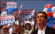"California gubernatorial candidate Arnold Schwarzenegger listens to the applause of supporters during a campaign rally on his ""California Comeback Express"" bus tour Thursday in Costa Mesa, Calif."