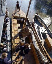 Members of the Discovery Expedition of St. Charles, Mo., speak to students from a keelboat docked next to a barge in Covington, Ky. The men are official re-enactors of the national 2003-2006 Lewis & Clark bicentennial commemoration and will retrace the entire waterway portion of the original 1803-1806 expedition. The keelboat is 55 feet long, and the pirogue docked to the right is 39 feet long.