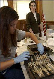 Kathy Richardson, a hazardous waste technician with the Lawrence Waste Reduction and Recycling Division, left, inspects an old doctor's bag from the collection of the Watkins Community Museum of History with museum director Rebecca Phipps. Employees at the museum recently opened the medicine bag and discovered a vial of nitroglycerin, used for certain heart ailments but also used in making dynamite.