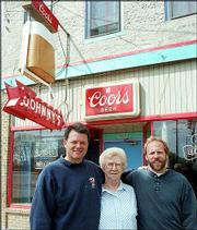Rick Renfro, left, Edith Wilson and Doug Hassig prepare for an anniversary celebration at Johnny's Tavern. Renfro and Hassig, who no longer is a co-owner of the bar, marked their 20th year of ownership in April 1998.
