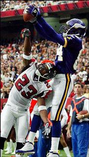 Minnesota wide receiver Randy Moss (84) pulls in a touchdown pass over Atlanta Falcons cornerback Kevin Mathis in the second half. Moss had two TD catches in the Vikings' 39-26 win Sunday in Atlanta.