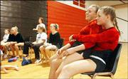 On the lap of her senior teammate Ellie Lloyd, Nicole Jones calms her nerves before competing in the parallel bars at the Lawrence All-Around Invitational. The gymnastics event was Monday at Lawrence High.