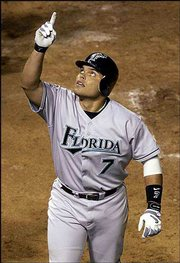 Florida's Ivan Rodriguez points skyward after hitting a three-run homer against the Chicago Cubs. The Marlins won, 9-8 in 11 innings, Tuesday in Chicago.