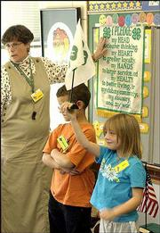 Sue Schmidt, left, an instructor in an after-school program at Kennedy School, helps students Xavier Wesemand-Wisdom, center, and Alix Caldwell recite the 4-H pledge Wednesday afternoon. The expiration of a $300,000 federal grant is putting the future of such programs in peril.