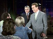 "California Gov.-elect Arnold Schwarzenegger, right, greets audience members as host Jay Leno looks on after Schwarzenegger walked on stage at the end of Leno&squot;s monologue during taping of ""The Tonight Show with Jay Leno."" Wednesday&squot;s appearance marked the first time Schwarzenegger had been on the show since Aug. 6, when he surprised everyone by announcing his candidacy for governor."