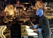 A Blue Man Group member jams on one of the act's many unusual percussion devices, backed by a live band on the Complex Rock Tour.