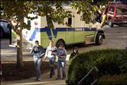Kansas University students pass Lawrence-Douglas County Fire & Medical vehicles outside Malott Hall on the KU campus. A laboratory in the building was evacuated Tuesday morning after two students lost consciousness and a third became ill within five minutes.