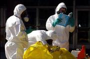 Officials in hazardous material suits examine evidence outside the Docking State Office Building in downtown Topeka. The 2,050 people who work in the building were evacuated Tuesday after an odor sickened four workers.