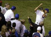 Cubs left fielder Moises Alou reacts after reaching unsuccessfully into the stands for a foul ball. The Cubs were unable to get a fan-interference call, and the play was key in Florida's eight-run eighth inning. The Marlins won, 8-3, Tuesday night at Wrigley Field in Chicago to even the NL championship series at three games apiece.