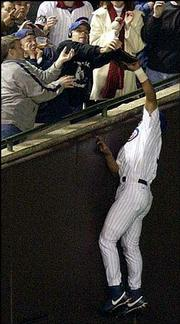 Chicago Cubs left fielder Moises Alou leaps for a foul ball as a fan interferes during the eighth inning against Florida. The Marlins scored eight runs in the inning en route to a 8-3 win Tuesday in Chicago, forcing a decisive Game 7 in the NL championship series.