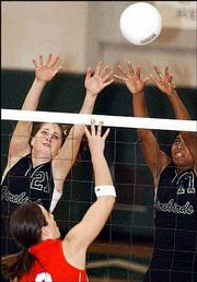 Free State's Katelin Karlin, left, and Kristin Baker sky for a block during the Free State quadrangular. The Firebirds went 1-2 on Senior Night Tuesday at the FSHS gym.