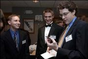 Kansas University freshmen Justin Klinger, left, from Overland Park, and Mark Mattione, center, Leawood, chuckle as Paul Karrer, Omaha, Neb., inspects a KU football ticket given as a gift from the university. The three were among 16 freshmen who received scholarships Friday from the Chancellors Club at the group's annual meeting at the Kansas Union Ballroom.