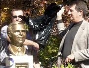 Brian Watson, Overland Park, left and Mark Watson, Temple, Texas, unveil a bust of their father, Buford Watson, at Buford M. Watson Jr. Park, Seventh and Kentucky streets. About 60 people attended the unveiling Sunday.