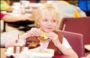 Hannah Reussner, 6, has a hamburger for lunch at Quail Run, along with apple sauce, chocolate cake and chocolate milk.