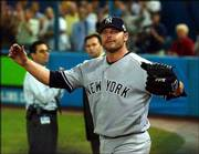 New York's Roger Clemens acknowledges cheers after getting the final out in the seventh inning.