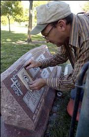 Robert Chitwood, who works for Lardner Monuments of Topeka, adds a picture to a grave marker in Oak Hill Cemetery. The stone was purchased several years ago from Lardner and a request for the picture came later, so Chitwood was finishing the job Tuesday.