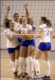 Kansas University volleyball players congratulate Ashley Michaels on her winning kill. From left are Andi Rozum, Josi Lima, Michaels, Jill Dorsey and Sarah Rome. The Jayhawks defeated Texas, 3-2, Wednesday night at Horejsi Center.