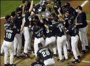 The Florida Marlins celebrate after winning Game 4 of the World Series against New York. Florida won, 4-3 in 12 innings, Wednesday night in Miami to even the series 2-2.