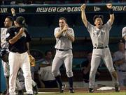 Florida's Ugueth Urbina, left, walks past the New York dugout as, from the left, players Derek Jeter, Hideki Matsui and Nick Johnson celebrate. The Yankees tied Game 4 in the ninth inning, before losing, 4-3, in the 12th Wednesday in Miami.