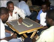 From left, players Kashka Jones, Ralph Mckenzie, Carlton Walker and Arthur Hall engage in dominoes at a games bar in Kingston, Jamaica. Dominoes long have been a favorite pastime in the Caribbean. Now, more than 500 of the world's best players are converging on Jamaica for the World Championship of Dominoes.