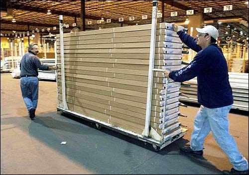 Amarr Garage Doors Vice President Of Manufacturing Delbert Phlipot, Left,  Helps Paul Ramirez Scoot Garage Door Panels Into The Delivery Area.