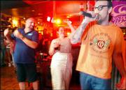 "Sean McKean, right, sings ""The Humpty Dance"" in front of a crowd gathered at Old Chicago on karaoke night. The bar and grill has since discontinued a regular karaoke night."
