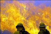 Lake Arrowhead firefighters battle a fast-moving brush fire in Rancho Cucamonga, Calif. About a dozen miles away, near San Bernardino, a wildfire destroyed 50 homes Saturday and forced thousands to flee.