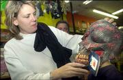 Jannel Munk, Lawrence, adjusts her son, Conner's monster mask. The two were shopping Saturday afternoon for at Fun 'n Games, 816 Massachusetts St., for Halloween costumes.