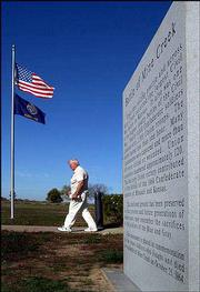 A visitor to the Mine Creek Battlefield, near Pleasanton, walks past a newly installed monument. The monument has sparked controversy with the Sons of Confederate Veterans, who want to place their own monument at the site.