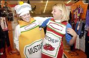 Kansas University sophomores, Becky Eschmann, Topeka, dressed as mustard, and Stefanie Crandall, Overland Park, wearing a ketchup get-up, look for Halloween costumes. The two shopped Monday at SuperTarget, 3201 Iowa.