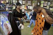 Dawn Martin watches as her husband, Clyde, sizes up a Fred Flintstone costume at Spirit Halloween Superstore in Broadview, Ill. Surveys show that more and more adults are celebrating Halloween with costume sales reaching higher percentages than in years past.