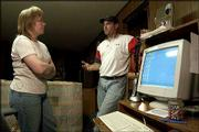 LaVon Wagoner, left, receives instructions from S&T Telephone Cooperative technician Shawn Dale, who installed high-speed Internet service in Wagoner's home in Colby. Small phone companies, like S&T, are bringing cutting-edge Internet services to rural Kansas.