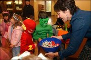 From left, 5-year-olds Griffin Nelson, Sammy Rosenstengle, and Braden Smith look over the candy selection offered by Robin Miller, an administrative specialist at the Kansas University law school. Students from Hilltop Child Development Center paraded their Halloween costumes Friday morning at KU and picked up some treats along the way.