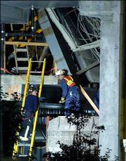Rescue workers talk as they search an area of a parking garage under construction that partially collapsed at the Tropicana Hotel and Casino in Atlantic City, N.J. A five-story section of the garage collapsed Thursday, killing four workers. The last victim was pulled from the site Friday.