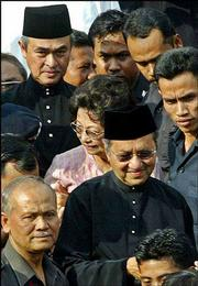 Mahathir Mohamed, front, wearing glasses, leaves the prime minister's office, followed by his wife, Siti Hasmah, and his successor, new Prime Minister Abdullah Ahmad Badawi, in Putrajaya, Malaysia. Mahathir stepped down Friday after a 22-year reign.