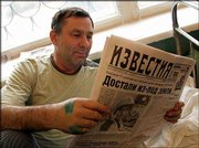 Rescued miner Valery Grabovsky reads the daily Izvestia in a hospital in Novoshakhtinsk, southern Russia. Grabovsky was among the Zapadnaya miners trapped in the mine when water burst in from an underground lake.