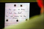 A note with five stars on it, found inside of a Ziploc bag at an Ashland Va., shooting scene on Oct. 19, 2002, is displayed on a screen Friday during testimony in the trial of sniper suspect John Allen Muhammad at the Virginia Beach Circuit Court.
