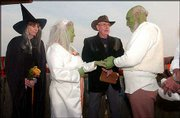 "Patty and Bob Gibbons tie the knot in a Halloween ceremony at Wells Overlook Park. The couple dressed as Shrek, a green ogre from the 2001 Dreamworks film ""Shrek."" Betty Caldwell, left, of Topeka, was the maid of honor. The Rev. Gary Thomas, center, of First United Methodist Church of Linwood, married the couple."