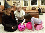 From left, Brooke Fox, 9, Noelle Fox and Sadie Fox, 3, evaluate their Halloween candy cache. The Fox family adopted Sadie in April 2001 after being her foster family since she was 6 weeks old.