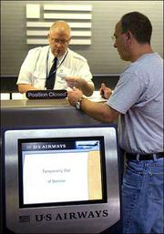 Jim Smyers, of Glen Allen, Va., gets his paperwork checked by a US Airways ticket agent, who declined to be identified, at Richmond International Airport in Richmond, Va. Smyers checked in using the automated kiosk, lower left, but had to go for human help when the machine's printer ran out of paper.