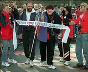 Zoe Koplowitz, center, who suffers from multiple sclerosis, crosses the finish line of the New York City Marathon on Nov. 4, 1996. Koplowitz, who usually takes more than 24 hours to finish the 26.2-mile course, today will participate in her 16th New York City Marathon.