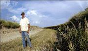 "Louis DeKeyser walks a portion of the Amazon Ditch near Lakin. DeKeyser oversees the operation of the 33-mile-long canal that supplies water to 16,000 acres of fields in western Kansas. Without the canal and irrigators, the area of the state would be settled only by ""rattlesnakes and pack rats,"" DeKeyser said."