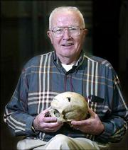 "Forensic expert Dr. William Bass holds a human skull with a bullet wound in his office at the University of Tennessee in Knoxville. Bass has co-authored a book from his extraordinary case files called ""Death&squot;s Acre."""