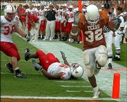 Texas running back Cedric Benson (32) crosses the goal line for a touchdown after racing past Nebraska's Barrett Ruud (38) and Titus Adams (96). Benson rushed for 174 yards and three touchdowns to help Texas defeat Nebraska, 31-7, Saturday in Austin, Texas.
