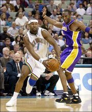 New Orleans' baron davis, left, drives around Los Angeles' Kobe Bryant. Davis had 23 points, 12 assists and four steals in the Hornets' 114-95 victory Friday night in New Orleans.