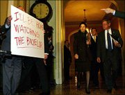 Sen. Tom Harkin, D-Iowa, far left, holds a sign up as Sen. Olympia Snow, R-Maine, center, and Sen. James Inhofe, R- Okla., right, walk into the Senate Chamber in Washington. The Senate started a session Wednesday for an all-night debate on President Bush's blocked judicial nominations.